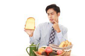 虫歯を治療後に食事をするか悩む男性